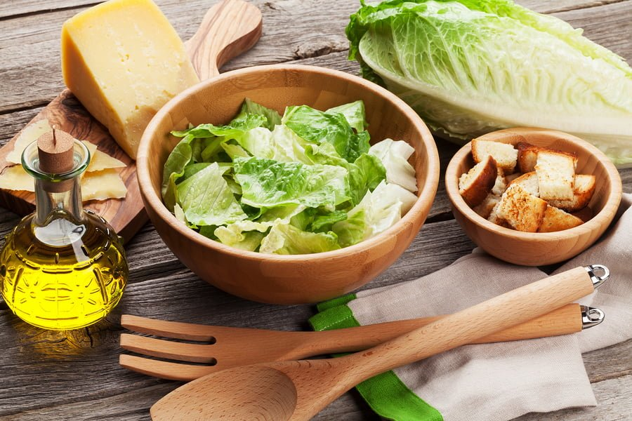 Fresh healthy caesar salad cooking on wooden table